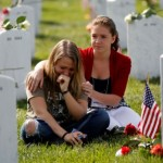 Heidi Heming, 27 yrs-old, left, of Chattanooga, Tenn.  is comforted by volunteer Marina Clifford, 12 yrs-old, while visiting a loved one's gravesite at Section 60 on Memorial Day at Arlington National Cemetery in Arlington, Virginia, Monday, May 27, 2013.  Iraq and Afghanistan war veterans are buried in Section 60. (AP Photo/Molly Riley)